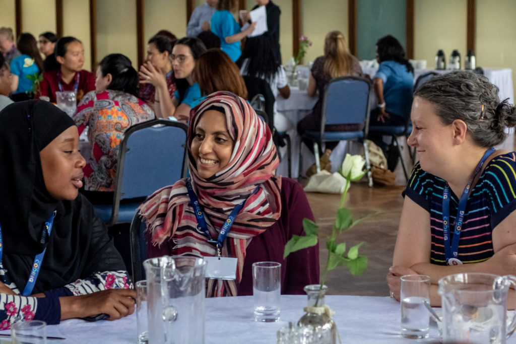 Three women sit at a table, talking. All are smiling. Two are wearing headscarves.