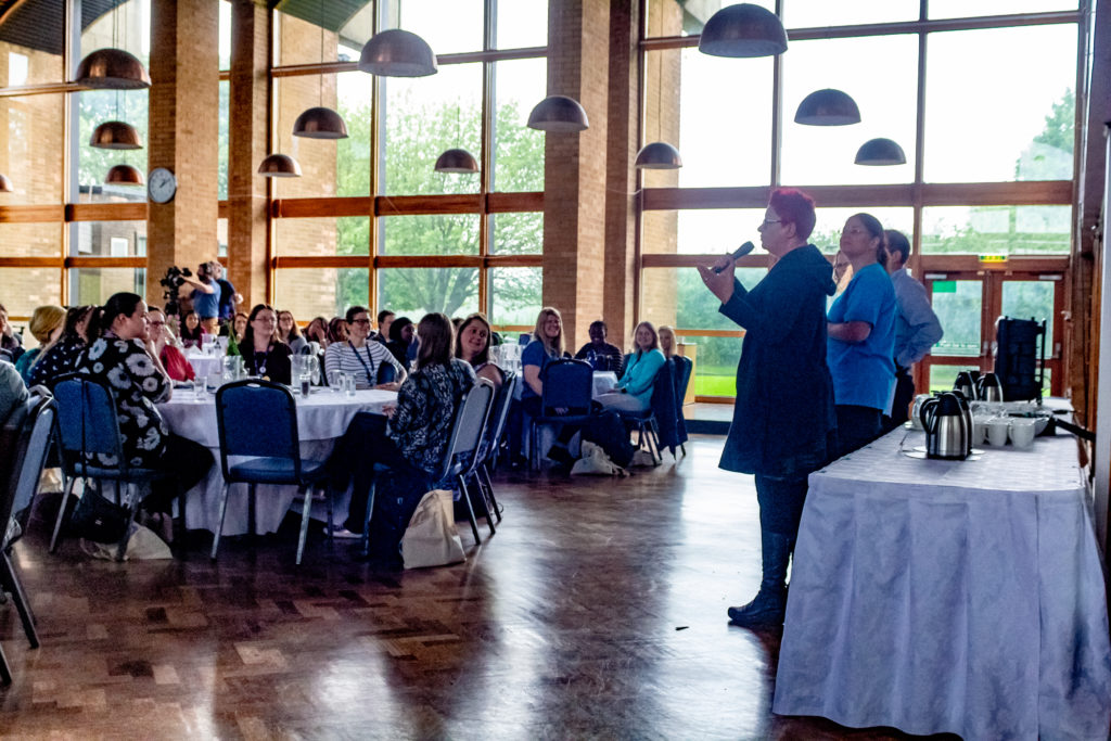 Two women address an audience in a large dining hall.