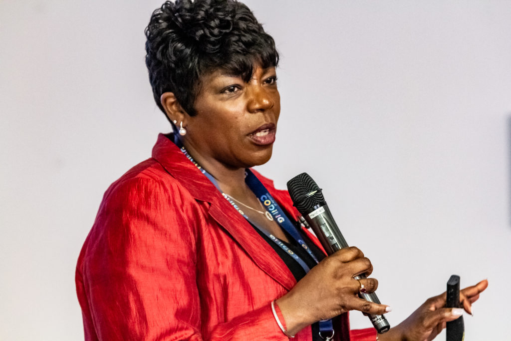 A BAME woman wearing a red jacket speaks into a microphone
