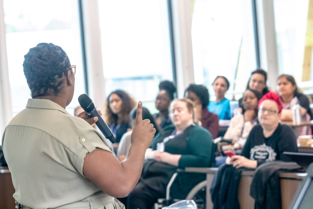 A BAME woman faces away from the camera, addressing an audience of women.