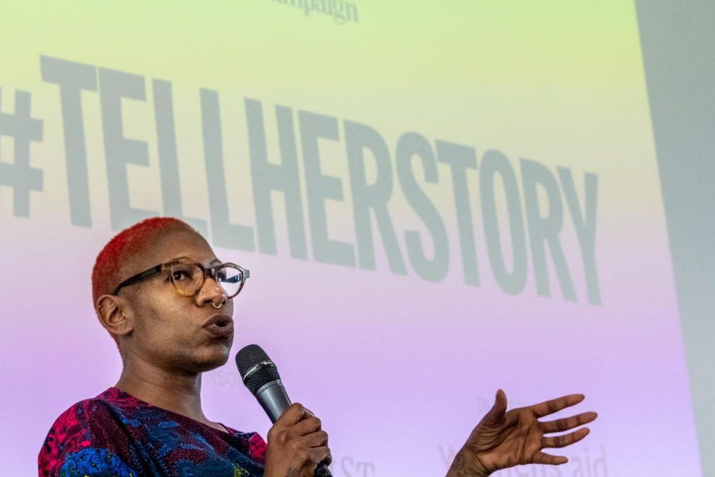 "A BAME woman wearing glasses speaks into a microphone, against a background which reads ""#TellHerStory"""