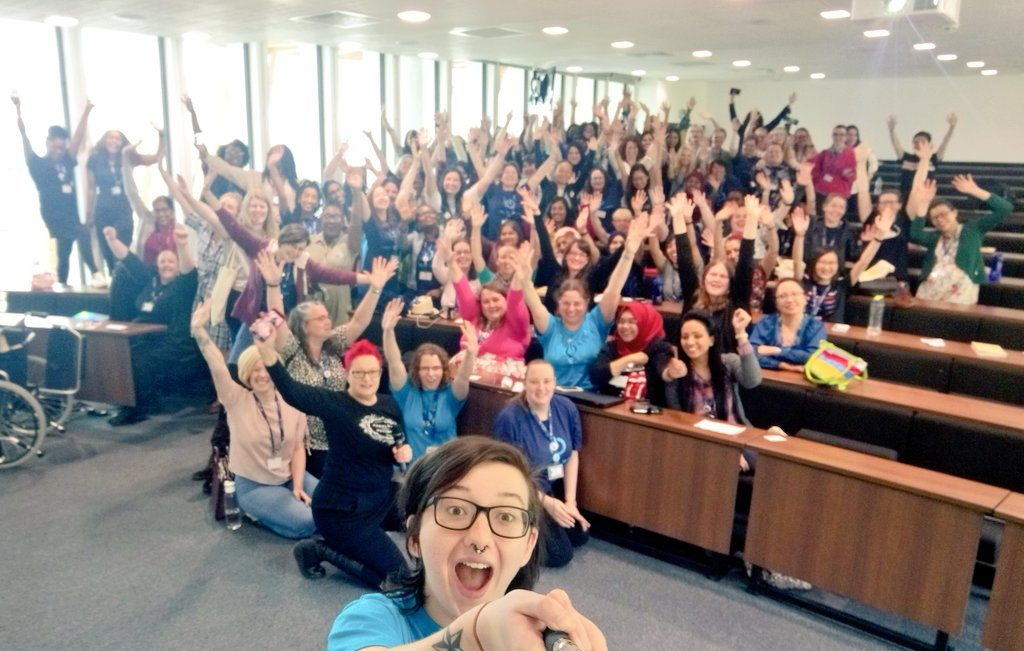 A group of women raise their hands in the air for a selfie