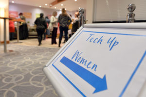 Image shows conference signage reading Tech Up Women with an arrow