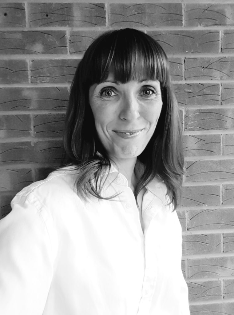 Black and white image shows a white women with long dark hair wearing a white shirt standing against a brick wall