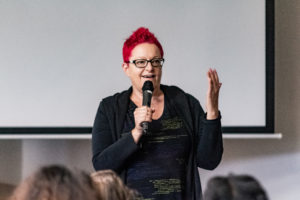 Image shows a white woman with short red hair and glasses speaking into a microphone