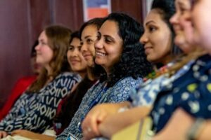 Image shows a row of diverse TechUPWomen smiling at something off screen