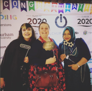 Picture of 3 women in front of a TechUPWomen Graduation backdrop holding props
