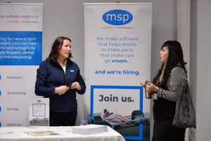 Two women talking in front of an MSP careers stand